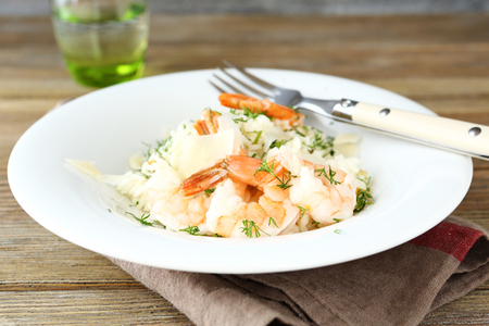 Tasty risotto with shrimp and dill on white plate, healthy food