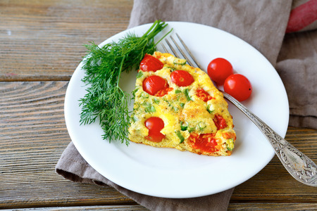 Frittata piece on white plate, wooden background
