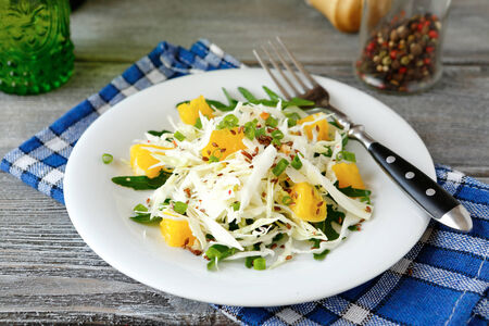 bord eten: Fresh cabbage salad and orange on a plate, food