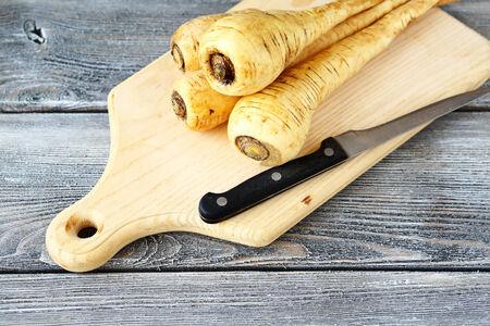 parsnip: Fresh Parsnip on a cutting board, healthy food Stock Photo