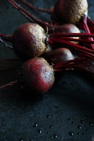armful: Armful of beets on a baking sheet, dark background