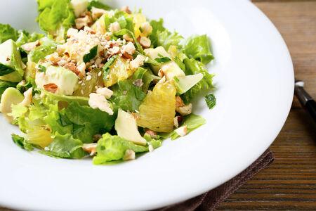 ensalada verde: Ensalada fresca con el aguacate, lechuga, naranja y nueces trituradas, comida de cerca