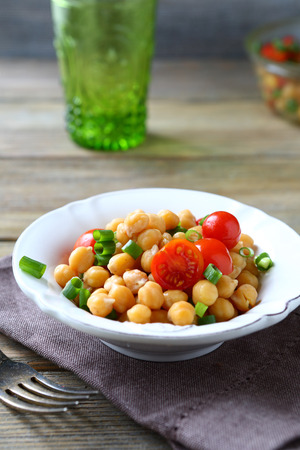 garbanzo bean: Delicious salad with boiled chickpeas and tomatoes, food
