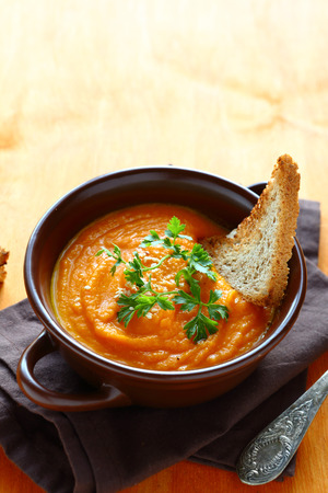 crouton: pumpkin soup with parsley and crouton, wooden background