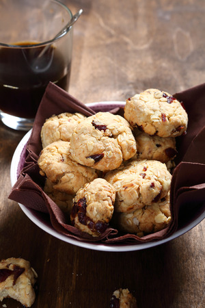 cofffee: Many cookies with cranberries in a bowl and coffee, food