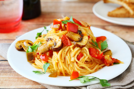 plato de comida: Espaguetis con champiñones y pimientos en un plato blanco, comida Foto de archivo
