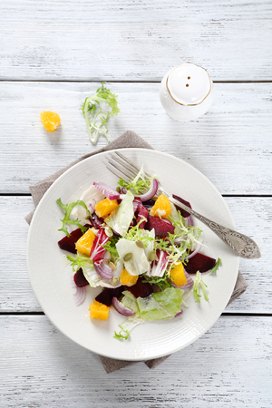 beets: Light salad with oranges on a plate, food
