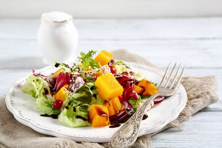 diet dinner: Salad with baked pumpkin on a plate, food