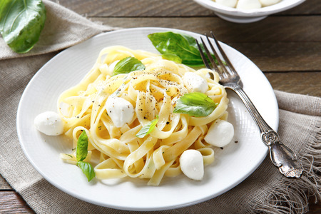 plate of food: Pasta with mozzarella and basil on a plate, food