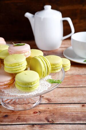 stand teapot: Macaroon on a stand with teapot and cup, food