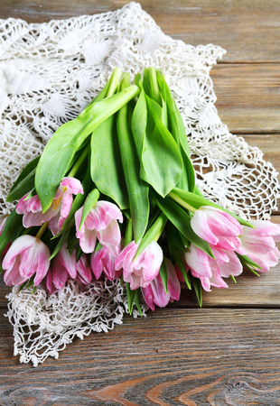 armful: Armful of pink tulips on the boards, flowers