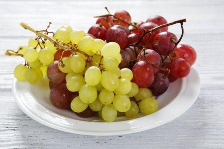 plate of food: Grapes on a white plate, food closeup