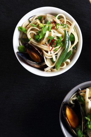 asian food: noodles with seafood in two bowls on slate dark background Stock Photo
