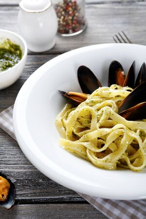 plate of food: Pasta with mussels on a plate, food