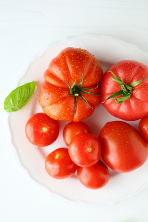 plate of food: ripe tomato on white plate, food top view