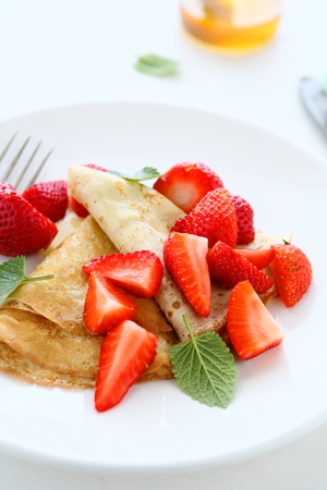 crepes with strawberries and honey, food closeup photo