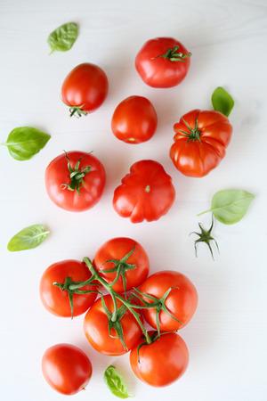 jitomates: los tomates frescos en el fondo de madera blanca, vista superior Foto de archivo