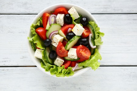 Fresh Greek salad in a bowl, top view