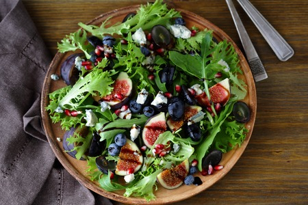 wooden plate: salad with figs, food closeup