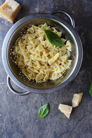 pasta: pasta in colander and cheese, food top view Foto de archivo
