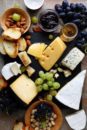 queso: varios quesos y uvas en la pizarra
