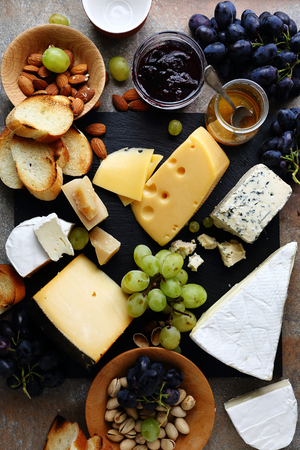 various cheeses and grapes on slate Stock Photo