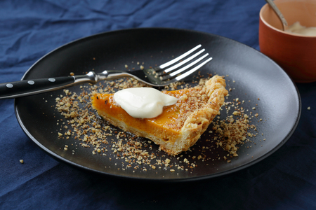 festive background: sweet pie with pumpkin and walnut on black plate