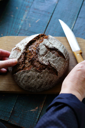 rustic food: cutting loaf of rustic bread, food cooking