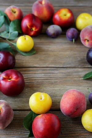 alycha: plums and peaches on wooden boards, fruits Stock Photo