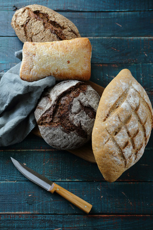 whole loaf breads on boards and knife Stock Photo