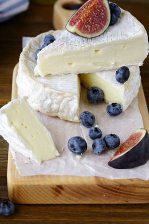 tabla de quesos: camembert cheese with figs and blueberries on board