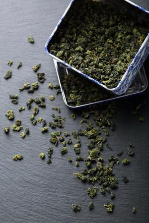 sencha tea: dried green tea leaves in box, food closeup