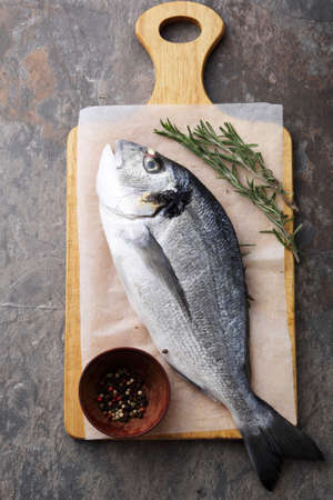 dorada: raw dorada fish on cutting board, top view Stock Photo
