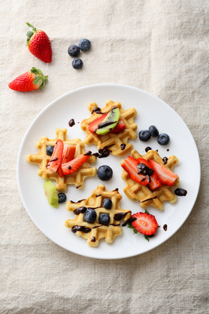 kiwis: belgian waffles with strawberries, blueberries and kiwis, food top view