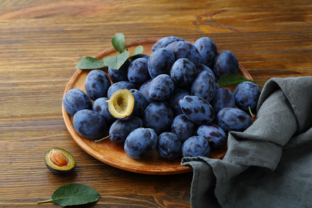 ciruela pasa: Fresh ripe prune on plate, fruits close-up