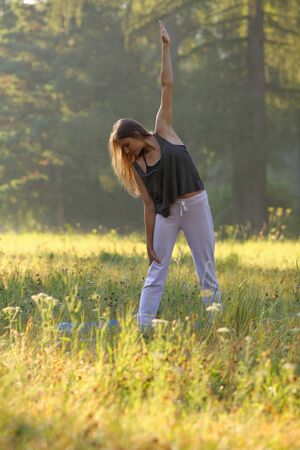 Beautiful girl doing exercise of yoga in nature Stock Photo