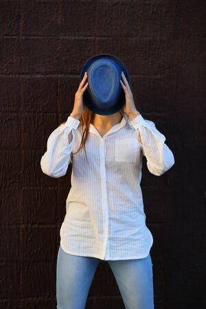 her: Cheerful girl holding hat hides her face