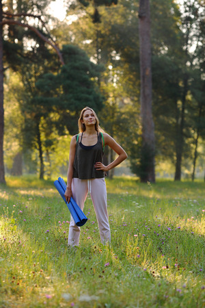 contemplates: Beautiful woman contemplates sunrise holding a blue yoga mat in the park