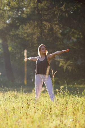 Girl smilling and practices yoga in park Stock Photo