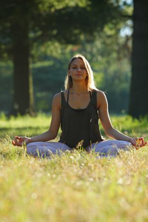 harmonizing: Beautiful yoga girl sitting cross-legged in the park Stock Photo