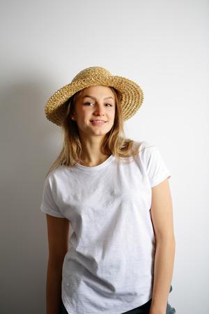 chapeau de paille: Smiling young woman standing in a straw hat Banque d'images