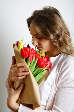 leaned: Feminine girl leaned over a bouquet of bright tulips, which is holding Stock Photo
