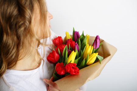 womens hands: Girl holding a bright bouquet of tulips. Concept March 8