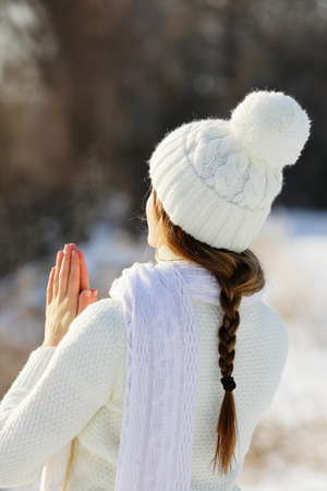 Girl in winter hat with pompom meditating outdoors