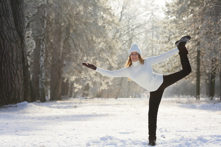 Yoga Smiling young woman standing on one leg in a winter fairy tale Stock Photo