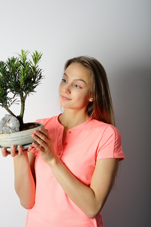 keep your hands: Young woman looking at bonsai and keep it in your hands