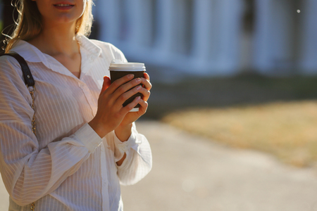 Woman holding cup coffee on walk Stock Photo