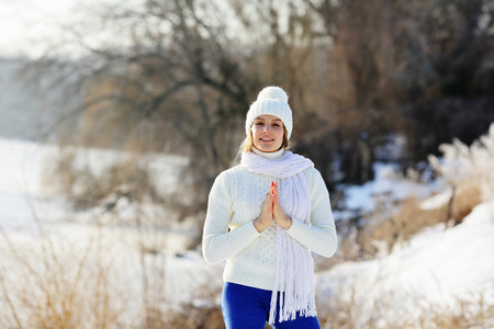 Healthy smiling woman standing on outside in winter park with praying hands Stock Photo