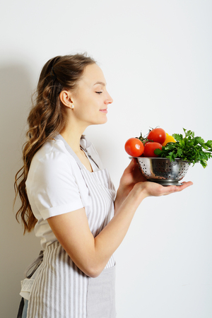 shef: Woman shef holding a colander with vegetables for salad