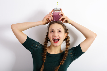 Beautiful girl holding a jar of smoothies on head